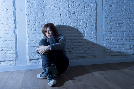 harsh light: teenager girl or young woman with red hair feeling sad and scared looking overwhelmed and depressed sitting on home floor in youth depression and suffering  problem in harsh contrast light