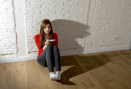 unwanted: sad and worried pregnant teenager girl or young desperate woman holding positive pink pregnancy test looking scared and devastated at home floor in unwanted baby and unexpected motherhood Stock Photo