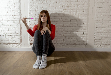 devastated: sad and worried pregnant teenager girl or young desperate woman holding positive pink pregnancy test looking scared and devastated at home floor in unwanted baby and unexpected motherhood Stock Photo