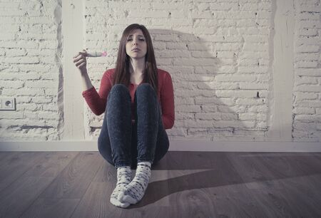 unexpected: sad and worried pregnant teenager girl or young desperate woman holding positive pink pregnancy test looking scared and devastated at home floor in unwanted baby and unexpected motherhood Stock Photo