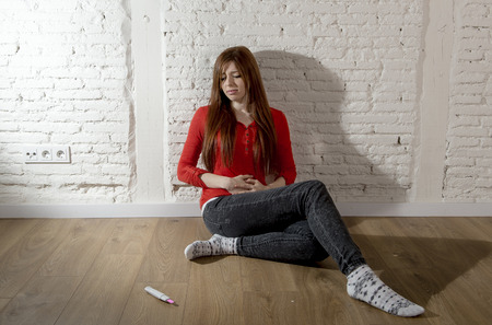 devastated: sad and worried pregnant teenager girl or young desperate woman looking to positive pink pregnancy test scared and devastated on floor in unwanted baby and unexpected motherhood Stock Photo