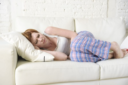 excruciating: young beautiful red hair woman with hand on her belly or tummy suffering stomach cramp and period pain lying on home couch in painful face expression female menstruation concept Stock Photo