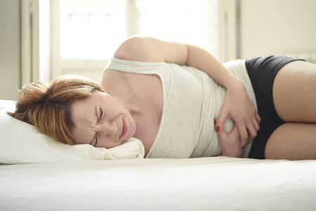 excruciating: young beautiful woman suffering stomach cramps on belly holding tummy with her hands in period pain lying on bed at home bedroom in soft lifestyle lighting set in menstruation hurt concept Stock Photo