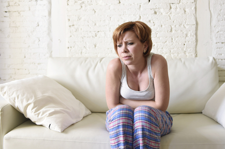 premenstrual: young beautiful red hair woman holding with her hands a hurting belly suffering stomach cramp and period pain sitting on home couch in sad face expression in female menstruation concept Stock Photo