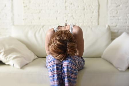 mooie jonge rode haren vrouw die met haar handen een kwetsen buik lijden maag kramp en menstruatiepijn zitten op de bank in huis vrouwelijke menstruatie begrip