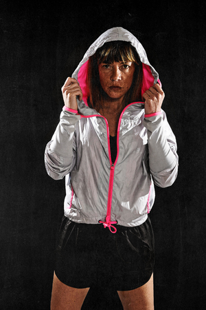 harsh: 40s fit and strong sport freckles woman wearing training jacket hood on posing defiant in cool attitude in gym club harsh light advertising style isolated on black background in fitness concept Stock Photo