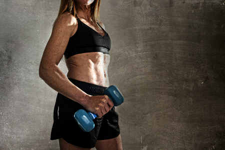 body built: faceless anonymous 40s fit and strong sport woman holding weight on her hand posing defiant in cool attitude with welt built body in gym club harsh light advertising style