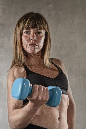 sixpack: 40s fit and strong sport freckles woman holding weight on her hand posing defiant in cool attitude with welt built body in gym club harsh light advertising style Stock Photo
