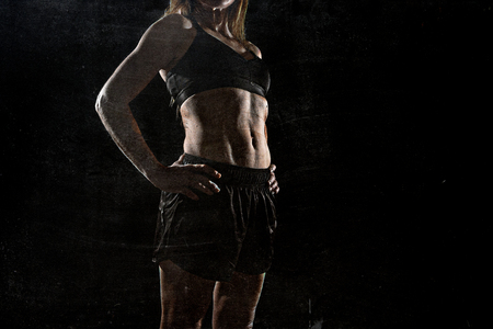 defiant: faceless anonymous 40s fit and strong sport woman holding posing defiant in cool attitude with welt built body in gym club harsh light advertising style isolated on black background