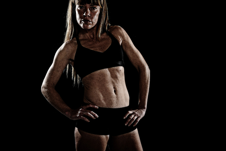 sixpack: 40s fit and strong sport freckles woman posing defiant in cool attitude with welt built body in gym club harsh light advertising style isolated on black background in fitness concept