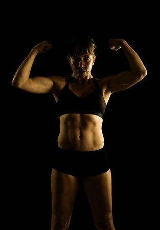 body built: 40s fit and strong sport freckles woman posing defiant in cool attitude with welt built body in gym club harsh light advertising style isolated on black background in fitness concept