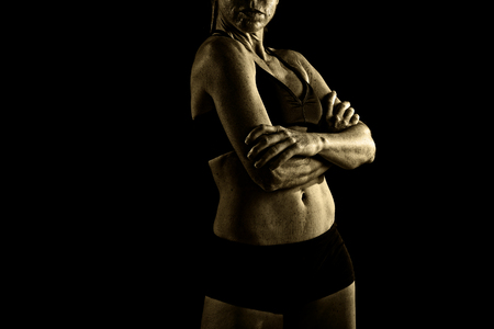 body built: faceless anonymous 40s fit and strong sport woman holding posing defiant in cool attitude with welt built body in gym club harsh light advertising style isolated on black background
