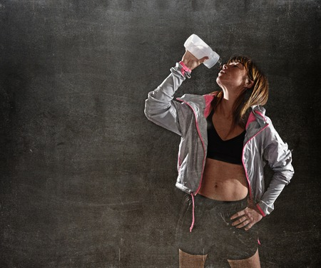 sixpack: 40s fit and strong sport freckles woman drinking water after training workout  in gym club harsh light advertising style isolated on black background in fitness concept