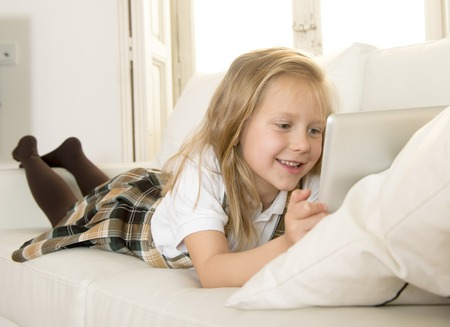 7 years old: sweet cute and beautiful 6 or 7 years old female child with blond hair in school uniform lying on home sofa couch using internet app on digital tablet pad playing online game smiling happy