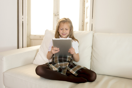 7 years old: sweet cute and beautiful 6 or 7 years old female child with blond hair in school uniform sitting on home sofa couch using internet app holding digital tablet pad playing online game smiling happy
