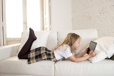 7 years old: young sweet cute and beautiful 6 or 7 years old girl with blond hair in school uniform lying on home sofa couch using internet app on digital tablet pad playing online game smiling happy
