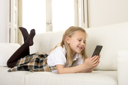 6 7 years: sweet cute and beautiful 6 or 7 years old female child with blond hair in school uniform lying on home sofa couch using internet app on mobile phone playing online game looking happy and relaxed