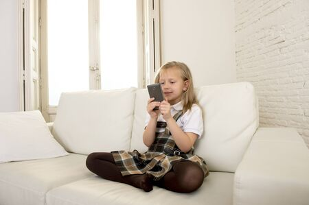 7 years old: sweet cute and beautiful 6 or 7 years old female child with blond hair in school uniform sitting on home sofa couch using internet app on mobile phone playing online game looking happy and relaxed