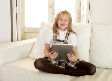 süße nette und schöne 6 oder 7 Jahre alt weibliches Kind mit blonden Haaren in der Schuluniform sitzt auf der Couch zu Hause Sofa unter Verwendung des Internet-app digitalen Tablet-Pad spielen Online-Spiel lächelnd glücklich Standard-Bild