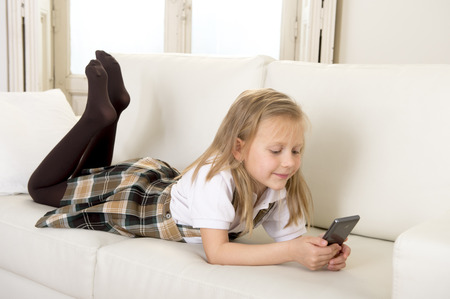 7 years old: sweet cute and beautiful 6 or 7 years old female child with blond hair in school uniform lying on home sofa couch using internet app on mobile phone playing online game looking happy and relaxed