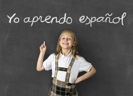 junior education: young sweet junior schoolgirl with blonde hair standing happy and smiling isolated in front of classroom blackboard holding chalk in children learning spanish language and education concept