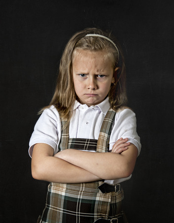 junior education: young sweet junior schoolgirl with blonde hair moody and sad face expression standing isolated in front of blackboard with arms crossed wearing school uniform in children education stress Stock Photo