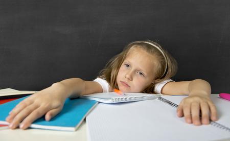 deberes: triste y cansado colegiala secundaria linda con el pelo rubio que se sienta en el estr�s de trabajo que hace la preparaci�n con aspecto aburrido y abrumado en la educaci�n de los ni�os en la escuela y bajo rendimiento acad�mico