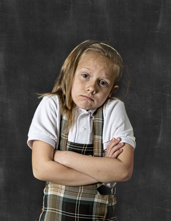 junior education: young sweet junior schoolgirl with blonde hair in sad face expression standing isolated in front of classroom blackboard with arms crossed wearing school uniform in children education stress