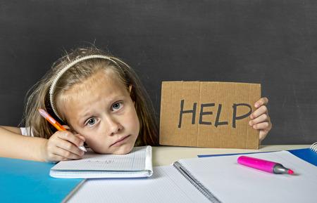 triste y cansado colegiala secundaria linda con el pelo rubio que se sienta en el estrés de trabajo que hace la preparación con aspecto aburrido y abrumado en la educación de los niños en la escuela y bajo rendimiento académico