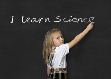 science text: young sweet junior schoolgirl with blonde hair standing happy writing with chalk on classroom blackboard I learn Science text in children learning at school and education concept Stock Photo