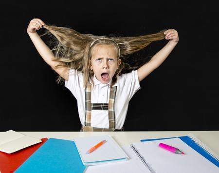 gekke schattige junior schoolmeisje zittend op het bureau in stress werken huiswerk trekken haar blond haar gek en overweldigd in kinderen onderwijs en op school hard werken