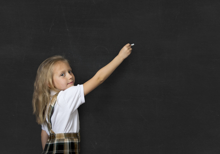 junior education: young sweet junior schoolgirl with blonde hair standing happy and smiling writing with chalk isolated in front of school classroom blackboard wearing school uniform in children education Stock Photo