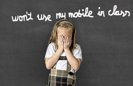 young sweet junior schoolgirl with blonde hair crying sad and shy standing in front of school class blackboard chalk written on forbidden use of mobile phones and cellular in school class