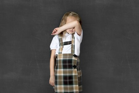 junior education: young sweet junior schoolgirl with blonde hair crying sad and shy standing isolated in front of school class blackboard wearing school uniform in children education stress