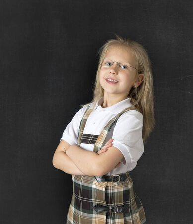 junior education: young sweet junior schoolgirl with blonde hair standing and smiling happy  isolated in blackboard background wearing school uniform in children education success and fun