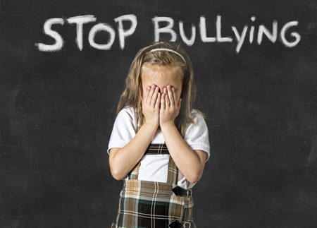 junior education: young sweet junior schoolgirl victim of bully crying sad standing in front of school class blackboard with chalk text stop bullying in school children bullied and education stress Stock Photo