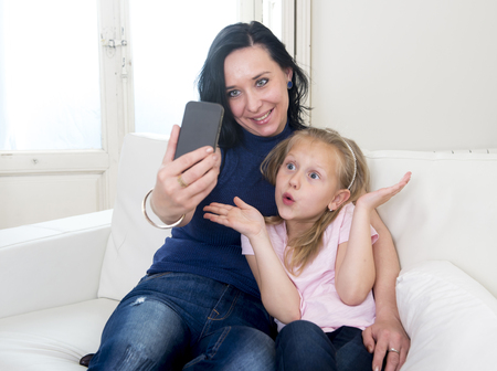 love pic: young happy woman with her little cute blond daughter taking selfie photo with mobile phone enjoying together at home sofa couch in mother and little girl self portrait picture concept