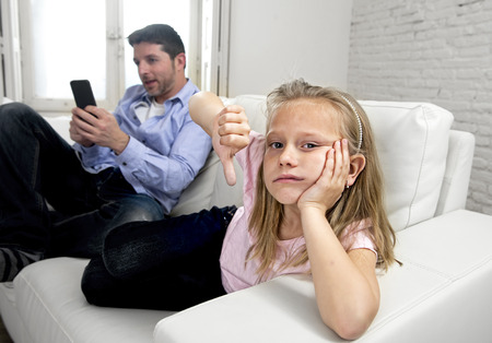young internet addict father using mobile phone ignoring his little sad daughter looking bored lonely and depressed feeling abandoned and disappointed with her dad in parent bad selfish behaviour