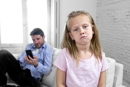 selfish: young internet addict father using mobile phone ignoring his little sad daughter looking bored lonely and depressed feeling abandoned and disappointed with her dad in parent bad selfish behaviour