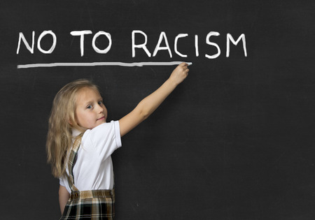 anti racist: young sweet junior schoolgirl with blonde hair writing with chalk no to racism in  classroom blackboard wearing school uniform in children education against racist behavior