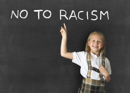anti racist: young sweet junior schoolgirl with blonde hair pointing with her finger to text no to racism written in classroom blackboard wearing school uniform in children education against racist behavior Stock Photo