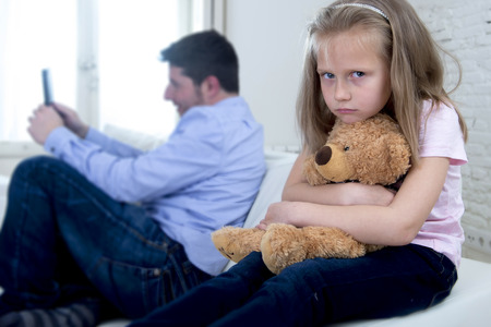 selfish: young internet addict father using mobile phone ignoring little sad daughter looking bored hugging teddy bear abandoned and disappointed with her dad in parent bad selfish behavior
