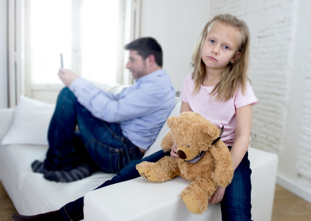 selfish: young internet addict father using mobile phone ignoring little sad daughter looking bored with teddy bear abandoned and disappointed with her dad in parent bad selfish behavior