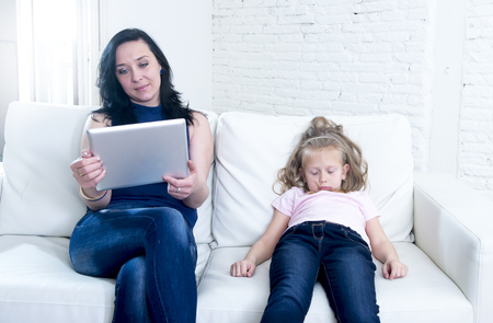 selfish: internet network addict mother using digital tablet pad ignoring little sad daughter left alone bored and depressed feeling abandoned and disappointed with mum in parent bad selfish behavior