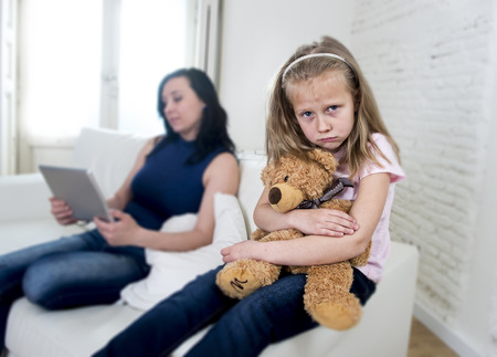 ignoring: young internet addict mother using digital tablet pad ignoring little sad daughter looking bored hugging teddy bear abandoned and disappointed with her mum sitting on couch sofa Stock Photo