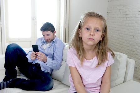 ego�sta: joven padre adicto a Internet utilizando el tel�fono m�vil hace caso de su peque�a hija triste que parece aburrida y solitaria sentimiento de depresi�n abandonado y decepcionado con su padre en la matriz mal comportamiento ego�sta