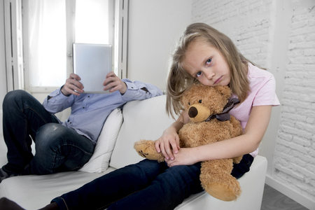 ignoring: young internet addict father using digital tablet pad ignoring little sad daughter looking bored hugging teddy bear abandoned and disappointed with dad sitting on home couch sofa