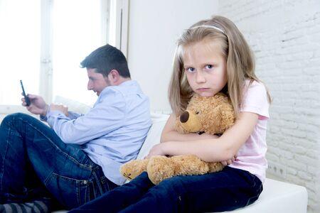 ego�sta: joven padre adicto a Internet utilizando el tel�fono m�vil haciendo caso omiso de la peque�a hija que parece aburrida triste que abraza el oso de peluche abandonado y decepcionado con su padre en la matriz mal comportamiento ego�sta