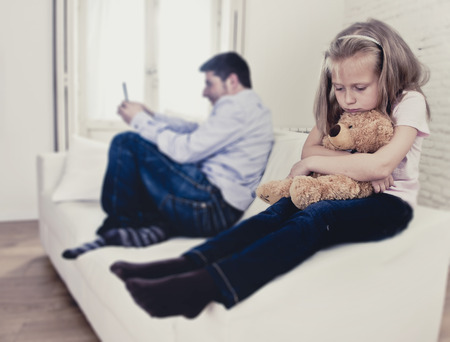 ignoring: young internet addict father using mobile phone ignoring little sad daughter looking bored hugging teddy bear abandoned and disappointed with her dad in parent bad selfish behavior