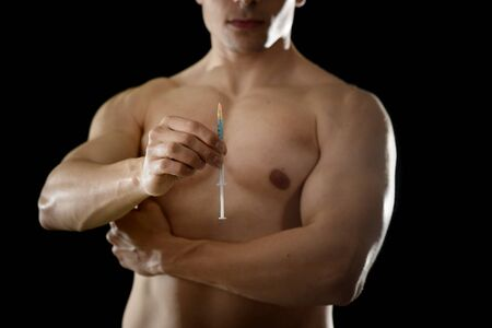 steroids: young body building sportsman using steroids for increasing sport and athletic  performance holding syringe isolated on back background in sport cheat doping and illegal use of hormones